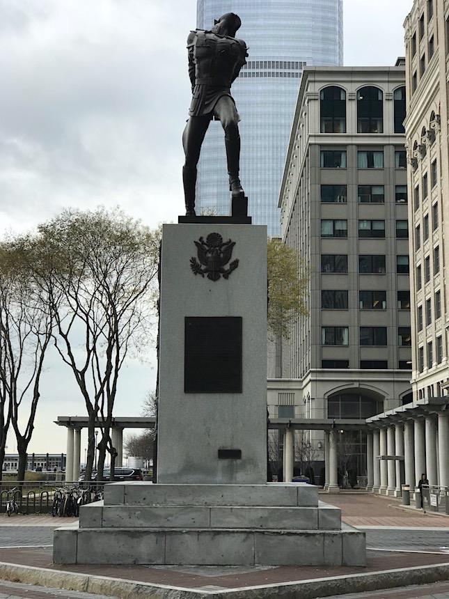 """Pomnik Katyński w Jersey City w stanie New Jersey nad rzeką Hudson jest według notatki w Wikipedii pierwszym pomnikiem katyńskim w Stanach Zjednoczonych. Odsłonięto go w maju 1991 roku. Unikam takich rzeczy, ale tym razem nie mam wyjścia i muszę posiłkować się informacjami z tego portalu. Z notatki z Wikipedii wynika że : """"Autorem monumentu upamiętniającego ofiary zbrodni katyńskiej popełnionej w 1940 roku przez radziecką policję polityczną NKWD na polskich jeńcach wojennych na plecenie Biura Politycznego KC WKP, jest polski rzeźbiarz Andrzej Pityński. Pomnik o wysokości około 12 metrów składa się z granitowego cokołu o wadze 120 ton, na którym znajduje się wykonana z brązu postać zakneblowanego żołnierza z rękoma związanymi z tyłu, z wbitym w plecy bagnetem nasadzonym na karabin. Rzeźba żołnierza ma wagę 6 ton"""". Pomnik usytuowany jest w pięknej scenerii, w tle rozpościera się panorama Manhattanu. Część Jersey City, w której się znajduje przechodzi od kilku lat zmiany a ich efektem jest nowoczesny, ciągnący się na kilka kilometrów deptak wzdłuż rzeki Hudson z widokiem na wieżowce Nowego Jorku. Pan X i ja nocowaliśmy kilka razy w tej okolicy w czasie naszych wypadów do Nowego Jorku, ponieważ można dostać się stąd na Manhattan w kilka minut za pomocą promów. Wielkim plusem nocowania po tej stronie rzeki są widoki i zdjęcia jakie można tu zrobić. O tym jak doszło do tego, że w New Jersey stanął Pomnik Katyński można przeczytać na tablicy znajdującej się na cokole : Na Pomniku Katyńskim znajduje się również pamiątkowa tablica upamiętniająca zamachy z 11 września. Wmurowano ją tutaj we wrześniu 2004 roku :"""